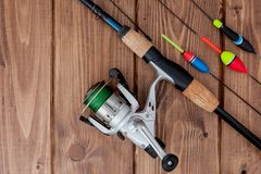 Fishing tackle - fishing rod fishing float and lures on beautiful blue wooden background, copy space.  stock photos