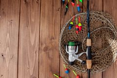 Fishing tackle - fishing rod fishing float and lures on beautiful blue wooden background, copy space.  royalty free stock image