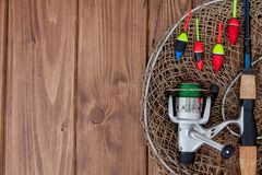 Fishing tackle - fishing rod fishing float and lures on beautiful blue wooden background, copy space.  stock photo