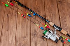 Fishing tackle - fishing rod fishing float and lures on beautiful blue wooden background, copy space.  royalty free stock photo