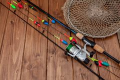 Fishing tackle - fishing rod fishing float and lures on beautiful blue wooden background, copy space.  royalty free stock images