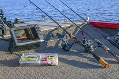 Fishing tackle set and fishfinder, echolot, sonar at the boat. Spinning rods with reels and lures royalty free stock image