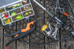 Fishing tackle set. Spinning rod with reel, lures, baits, lip grip and landing net on wooden platform.  stock image