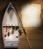 Fishing Tackle - Small Boat. Brown wooden wall with a small boat, fishing tackle and empty parchment Royalty Free Stock Photography