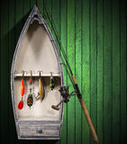 Fishing Tackle - Small Boat. Green wooden background with small boat and fishing tackle Royalty Free Stock Images