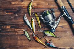 Fishing tackle - fishing spinning, hooks and lures on wooden background stock image