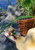 Fishing tackle with wicker basket and hat on the background Stock Image