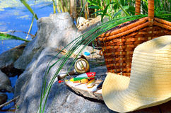 Fishing tackle with wicker basket and hat on the lake Royalty Free Stock Photos