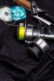 Fishing tackles on black jacket Stock Image