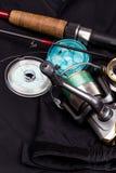 Fishing tackles on black jacket Stock Photo