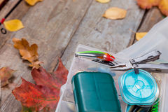 Fishing tackles on board with leafs of autumn Royalty Free Stock Photo