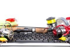 Fishing tackles on computer keyboard Royalty Free Stock Photography