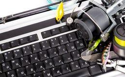 Fishing tackles on computer keyboard Stock Image