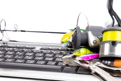 Fishing tackles on computer keyboard Stock Images