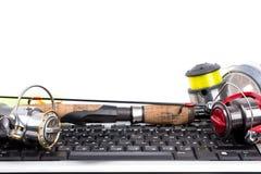Fishing tackles on computer keyboard Royalty Free Stock Photos