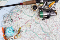 Fishing tackles - rod, reel, line and lure on map Stock Images