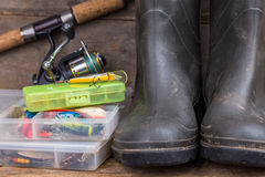 Fishing tackles and rubber boots on timber board Royalty Free Stock Image