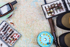 Fishing tackles and shoes on paper map Royalty Free Stock Image