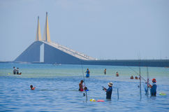 Fishing Tampa Bay by Sunshine Skyway Bridge. People fishing and swimming in Tampa Bay Florida by the iconic Sunshine Skyway Bridge on a beautiful sunny afternoon royalty free stock image
