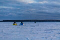 Fishing tents on the frozen and snow-covered lake