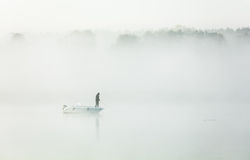 Fishing in a thick morning fog. A man fishing from a boat on a lake in a thick morning fog Royalty Free Stock Photo