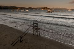 Fishing in Tolo, Greece. Lonesome fishing at dusk, sky, retirement, horizon, coast, relaxation, catch, outdoors, cast, casting, dawn, hobby, vacation, rod royalty free stock images