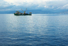 Fishing Trawler. Single small fishing trawler leaving the harbor into the the blue Aegean sea to go fishing on a cloudy winter's day Royalty Free Stock Image