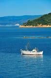 Fishing trawler among Greek islands. White fishing trawler anchored among islands of the Aegean Sea Royalty Free Stock Photo