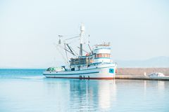 Fishing trawler moored in the beautiful harbor of a small town Postira - Croatia, island Brac. Fishing trawler moored in the beautiful harbor of town Postira Royalty Free Stock Photos