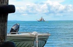 Fishing trawler & motor boat dinghy at sea stock photography