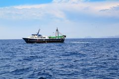 Fishing trawler professional boat working. In blue ocean sea Royalty Free Stock Photography