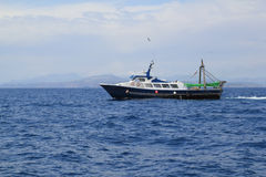 Fishing trawler professional boat working. In blue ocean sea Stock Images