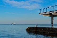 The fishing trawler sails by the sea. Passing along the coast and the old pier with two tiers Royalty Free Stock Photography
