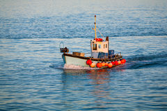 Fishing trawler at sea. Fishing trawler heads for the harbour at the end of the day as the sun goes down Stock Photography