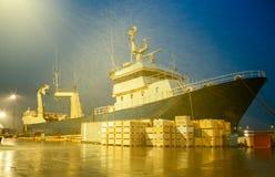 Fishing trawler ship at dock by night in drizzling rain Stock Photo
