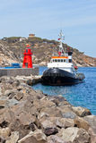 Fishing Trawler and Small Red Lighthouse Royalty Free Stock Photos
