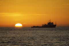 Fishing trawler at sunrise. Fishing vessel trawling off the East Coast of the UK at sunrise. The trawler is shown in silhouette against a natural vivid orange Royalty Free Stock Photo