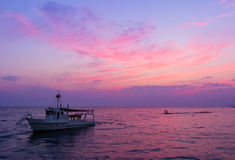 Fishing trawler on the water and dramatic clouds at sunrise Royalty Free Stock Image
