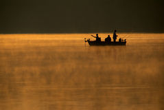 Fishing Trip. Three early morning fishermen enjoy a quiet morning on the lake royalty free stock photos