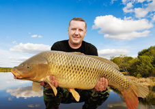 Fishing trophy. Angler with carp to 32 pounds at sunset Royalty Free Stock Image