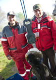 Fishing trophy. Two fishermen proud of a giant cod hanging on a fishing scale stock image