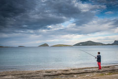Fishing under heavy cloudscape Royalty Free Stock Images