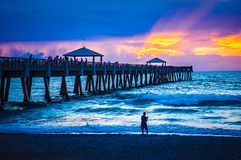 Fishing on and under the Juno Beach Fishing Pier. Sunrise over the fishing pier in Juno Beach, Florida as people fish on the pier and the beach stock photography