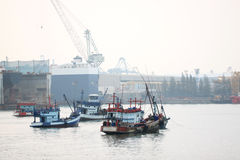 Fishing vessel and cargo ship in port. Royalty Free Stock Image