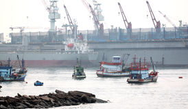 Fishing vessel and cargo ship in port. Stock Photos