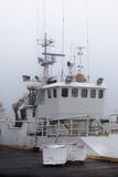 Fishing vessel in a foggy misty morning at Harbor Stock Photography