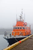 Fishing vessel in a foggy misty morning at Harbor Stock Photos