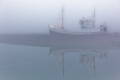 Fishing vessel in a foggy misty morning Stock Image