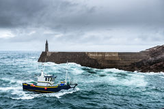 Fishing Vessel under Storm arriving at pier Stock Photo