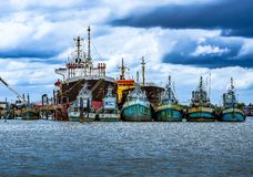 Fishing vessels and large shipping vessels in the sea. On the da royalty free stock image